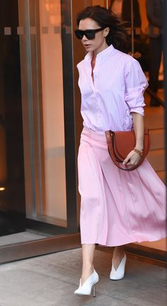 On Victoria Beckham: Victoria Beckham sunglasses, shirt, bag, and skirt