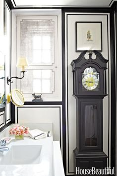 Without the moisture and humidity from a shower to worry about, an heirloom-worthy grandfather-style clock can have pride of place. Ideal for filling a narrow span of wall, the timepiece complements the nattiness of the tailored bands of black paint. Click through for more powder room decorating ideas.