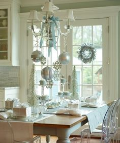 Overhead Opulence~ Don't restrict magnificent baubles and sparkly snowflakes to the tree. Accentuate overhead lighting with shimmery decorations and stick to a fresh winter palette like pale blue and silver. Finish it off with an elegant satin ribbon gently dangling from the chandelier.