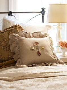 Use an embellished pillow sham with vintage brooches to mimic the intricacy of fine embroidery.