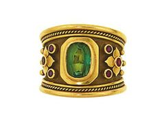 A tourmaline and ruby-set 18ct gold dress ring, by Elizabeth Gage   The wide tapering band with ropetwist detail collet-set to the centre with an oval-cut green tourmaline, between floral design shoulders set with circular-cut rubies, finger size O, London hallmark  Signed Gage