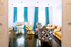 The 11 Greatest Lessons We Learned From Jonathan Adler // living room, orange sofa, Pedro Friedeberg chairs, grand piano, teal curtains