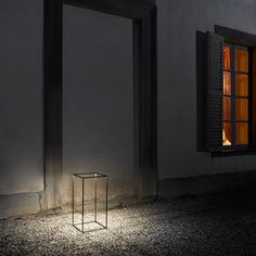 FLOS IPNOS Outdoor Lamp casts a bright glow outside the home on a stone walkway, as it feels a seemingly blank space with beautiful light.