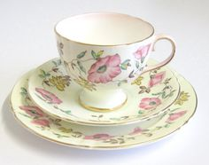 This is a very pretty scallop-edged trio in the palest green with a hint of pink blush to the handle and the inside rim of the cup, hand coloured with pretty pink roses and foliage. The set would have been made between 1945 and 1963 by the English firm of Sampson Smith under their trade name Old Royal. It is in very good condition with no chips, cracks, crazing or wear to the pattern/gilding. There is a small mark under the glaze on the plate (see enlargement of fourth photograph) and a...