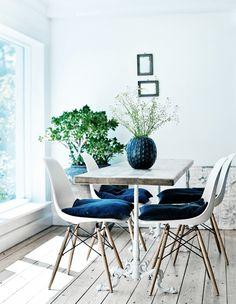 Nostalgischer Esstisch mit vier Eames Stühlen auf Parkett und bodentiefen Fenstern