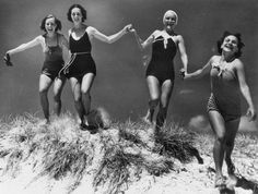 1930s or 1940s group of girls in their bathing suits running through the sand at the beach. vintage swimwear, girls at the ocean, happy good times during the Great  Depression