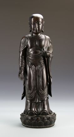 China, antique Zitan Buddha figure, standing, with elaborate robes and a serene expression, the head does not have hair or headdress, on a double lotus base. Height 15 1/2 in.