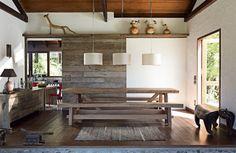 O painel de correr de madeira de demolição (2 x 2,30 m) oferece a opção de integração entre cozinha e sala de jantar ou de total independência entre elas. O trilho, do mesmo material, dá origem a uma prateleira, suporte para a coleção de arte indígena do casal.