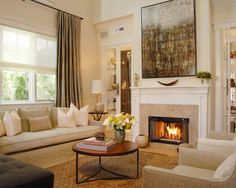 Nice living room with big window, quality built-ins behind glass doors, and simple fireplace. Large artwork above the fireplace mantel blends in colors and adds warmth to the room.
