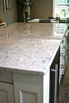 Beautiful White cabinet and carrara marble countertop is a major feature in this Rhode Island Kitchen.  The white island with furniture legs seating for 5 and wine and mini fridge is a chef's dream. Modern and sleek is the design feature which was achieved by the implementation of Modern Clear glass globe pendants, Black and chrome bar stools,Blue glass mosaic backsplash, brushed nickel bar pulls and finally a weathered oak floor.  Simply stunning! #RhodeIslandKitchen #CypressDesignco.