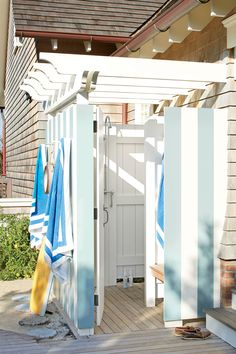 """My inspirations were blue skies, sand, and sea,"" says designer Meg O'Kane of her Jersey Shore home's beachy color scheme. A classic arbor ceiling tops off the look. The stripes are painted Dix Blue by Farrow & Ball."