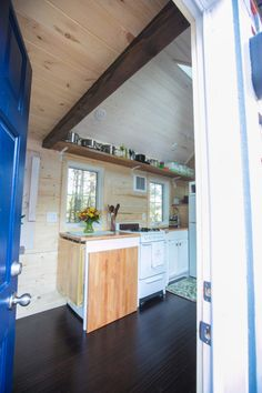 big wooden square folds up for a table/counter and 2 small benches are hanging from counter under flowers....space saver Hogan Tiny House Family 005