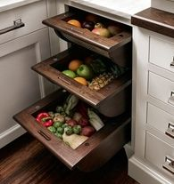 Vegetable and fruit baskets in walnut warm up this traditional kitchen by Peter Cadamone for Quality Custom Cabinetry Inc. and help keep countertops free of clutter. | Via Zillow.com