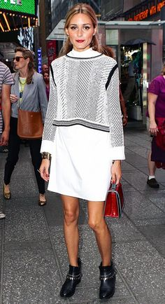 Olivia Palermo wears a patterned sweater, shirtdress, ankle boots, and a top-handle bag