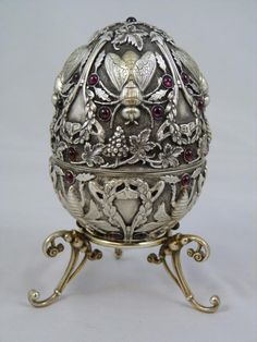 PAVEL OVCHINNIKOV RUSSIAN SILVER INSECTS EGG - This magnificent Russian silver egg adorned with cabochon garnets throughout has a raised design depicting flies, bees, leaves and grape clusters. Gold wash to interior. Makers marks to both pieces of the egg. Includes figural grape cluster silver stand. Late 19th century.