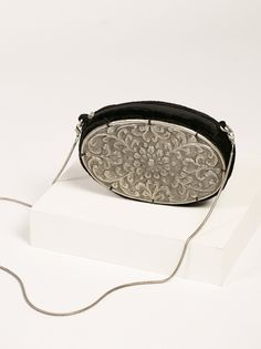 Scarlet Metal Crossbody   Featuring a vintage-inspired metal design this velvet crossbody has a snake chain strap. Lined interior with a zip top closure.