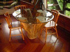 Um tronco serve de base à esta mesa com tampo de vidro. :)