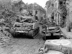 US troops pause in the streets of the devastated German city of Linnich. M4A3 Sherman tank and Dodge WC-52 next to it. 84th Infantry Division, April 24,1945.