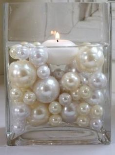 centerpiece made of pearl beads and floating candle- these are pretty much my style in a candle - w/ light blue beads/ornaments instead of champagne/ivory