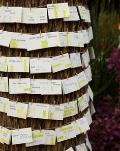 Table numbers and escort cards stamped with DIY designs dangle from a clothesline wrapped neatly around a large tree.