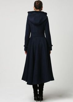 This stunning long woman's coat is beautifully fitted and tailored for a classic, feminine design. It features a slim fitting bodice with elongated sleeves and tapered waist band leading into a long, flowing skirt. The hood, shoulders and sleeve cuffs have a pretty ruffle detailing that really sets it apart. Lined in imitated silk, this coat also has deep side pockets and a three, fabric-covered button closure. To see in pink and red…
