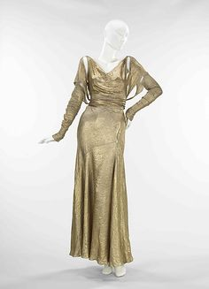 Lamé, a fabric which incorporates metallic threads and is known for its festive brightness, was often used in evening wear of the 1920s, '30s and '40s. The lamé used here is in relatively bright condition, allowing one to imagine its original effect of shining like liquid metal