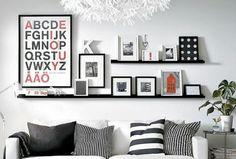 Une déco en noir et blanc avec des cadres posés sur une étagère.