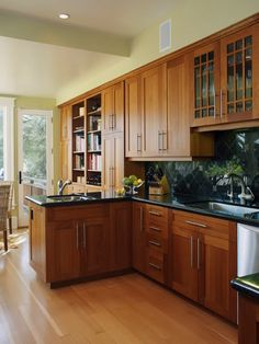 Cherry cabinets and light wood floors with dark granite counters - like handles on cabinets