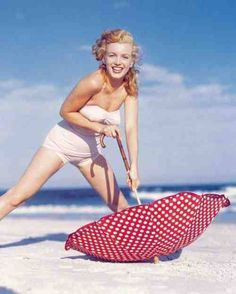 """1949. Marilyn at Tobey Beach - Long Island . Photo session with umbrellas. """"Red umbrella with white dots"""". Photo by Andre de Dienes."""