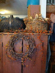 Love. put grapevine wreath on hoosier cabinet w/ orange berries