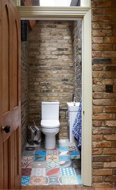 Small rustic bathroom with brick walls and skylight