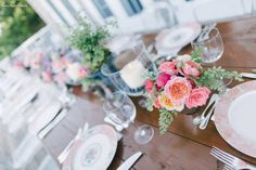 Beach wedding in Avalon, NJ.  Centerpieces consist of garden roses, green amaranthus, clematis, tweedia, maiden hair fern and kiwi vine. Also accenting this rustic table were glass hurricanes for pillar candles along with small potted herb plants.  Nancy Saam Flowers
