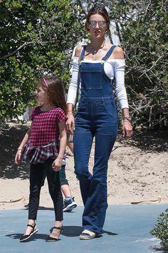 Alessandra Ambrosio, con peto vaquero con campana de Frame Jeans, camiseta blanca de manga larga y escote barco y alpargatas de Chanel.