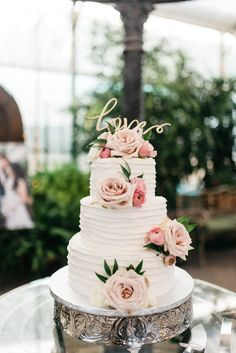 3 tier white wedding cake with soft pink fresh roses.