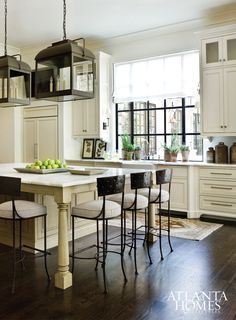 A collaboration between interior designer Amy Morris and kitchen designer Cynthia Ziegler, the kitchen boasts a pair of Paul Ferrante lanterns and leggy seating.