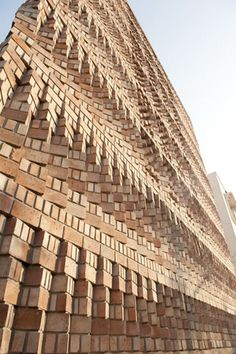 Brick facade shielding the South Asian Human Rights Documentation Centre in India, doing double duty as a solar screen and noise buffer. Layered Architecture, Detail Architecture, Asian Architecture, Brick Architecture, Amazing Architecture, Unusual Buildings, Amazing Buildings, Solar Screens, Shop Facade