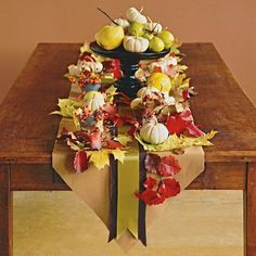 Scatter fall leaves and mini pumpkins on a wool table runner for a cozy table decoration. Plus, check out 15 more inspiring ideas for fabulous fall centerpieces.