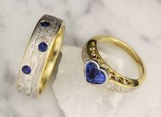 This mokume set features our Mokume Curls Engagement Ring with a beautiful heart shape blue sapphire and a matcching wedding band with flush sett blue sapphires, both in our White Mokume Gane.