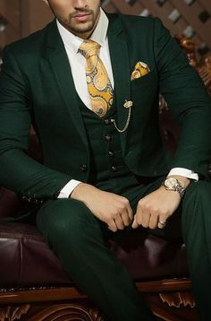 Dark green is a natural match for gold accents of any kind. Brass buttons, gold jewelry, or even a dark cream-colored shirt make logical pairings for a dark green suit.