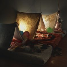 Simple kids bunkroom using old sheets for tents and mattresses on the floor.