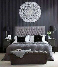 Gray, white and black is the name of the game with gray striped wall paper, tufted bed as well as seat, and linens.. Accented with blacks and whites, the room has very appealing, clean lines to it..