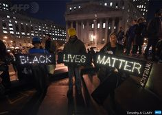 UNITED STATES, New York : Protesters stand in Foley Square in New York City on December 4, 2014 during demonstration against the chokehold death of an unarmed black father-of-six by a white police officer. It is the second consecutive night that demonstrators took to the streets of New York to condemn a grand jury's decision not to indict the officer over the July 17 death of Eric Garner. AFP PHOTO / Timothy A CLARY