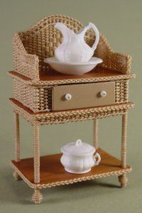 """Wicker & cherry wash stand with one drawer and shelf. Wicker has diamond pattern, braid trim, wrapped legs and ball feet. 1:12 Scale Dollhouse miniature. Measurements: 1 1/2""""D x 2 3/4""""W x 3 1/4"""" H."""