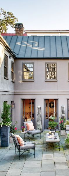 The entrance to this Charleston, South Carolina, kitchen house — now a guesthouse — opens onto a bluestone courtyard with seating by Janus et Cie.