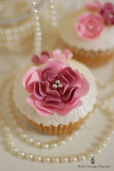 Fancy cupcakes with silver balls and string pearl table accents.  This would make a pretty presentation on a dessert buffet.
