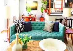 Tufted teal sofa with navy pillows