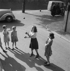 Spelende kinderen op straat meisjes kaatseballen Amsterdam