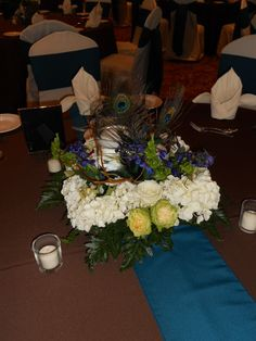 Mixed centerpiece with hydrangea, roses, ochids, bells of Ireland, delphinium, peacock feathers and floating candles