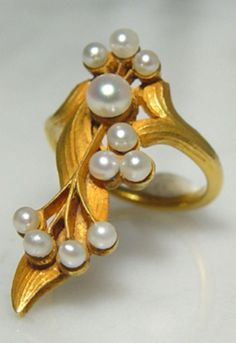 An Art Nouveau Gold and Pearl Ring, Circa 1900. 18k gold, formed as an asymmetric spray of leaves and flowers, set with eleven pearls. #ArtNouveau #ring