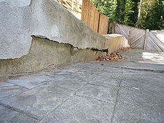 Sink hole under driveway/retaining wall.